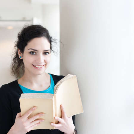 Portrait of a young woman reading a book with copy space photo