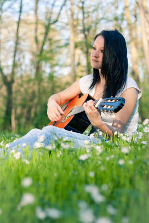 art therapy: Young woman playing the guitar outdoors
