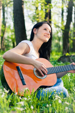 Young woman playing the guitar outdoors photo