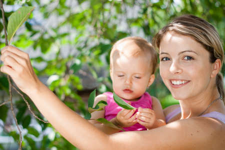 Young mother playing with her baby girl outdoors in the garden  Stock Photo - 16498660
