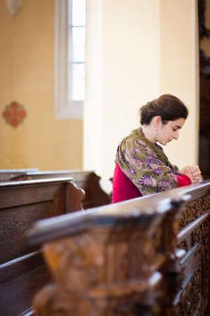Young woman praying in a church Stock Photo - 16498631