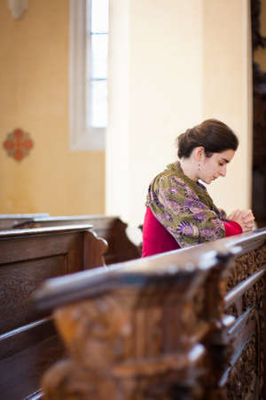 Young woman praying in a church Stock Photo - 16498631