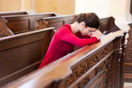 Giovane donna che prega in una chiesa