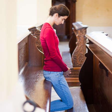 humility: Mujer joven rezando en una iglesia