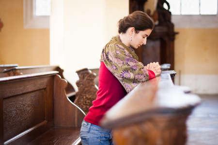 Mujer joven rezando en una iglesia Foto de archivo