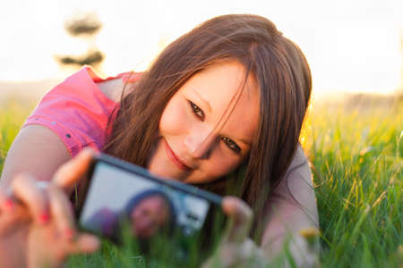 Teenage girl taking a photo of herself with her smartphone Stock Photo