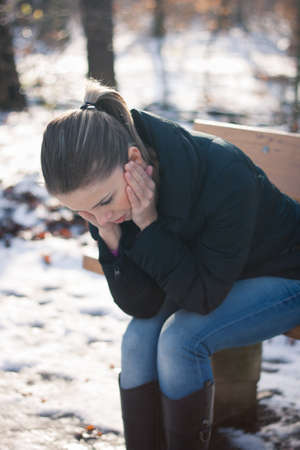 Closeup portrait of a depressed young woman sitting on a bench outdoors on a cold winter day photo