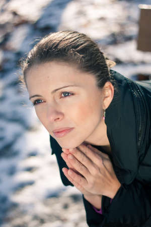 relationship problems: Closeup portrait of a depressed young woman sitting on a bench outdoors on a cold winter day