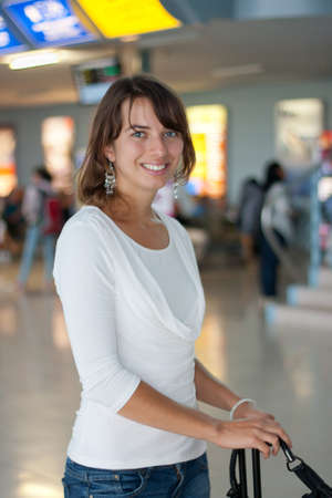 Pretty young woman at the airport, waiting in the departure hall before her flight photo