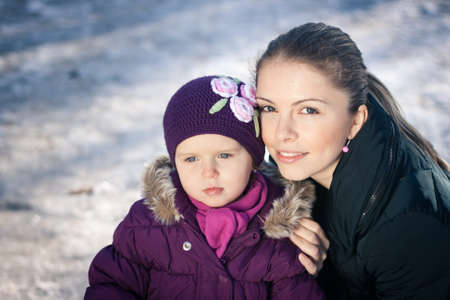Portrait of a beautiful young mother and her baby girl outdoors on a snowy winter day Stock Photo - 16987182