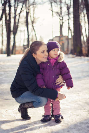 Young mother and her baby girl outdoors on a snowy winter day Stock Photo - 16987183