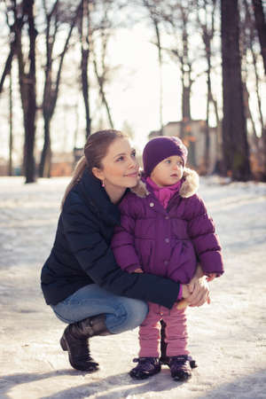 Young mother and her baby girl outdoors on a snowy winter day Stock Photo - 16987189