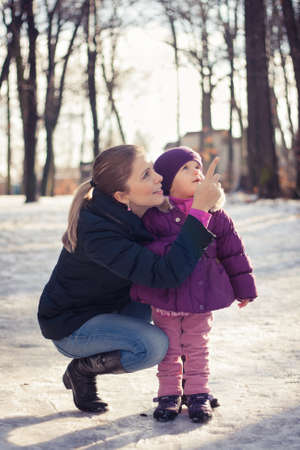 Young mother and her baby girl outdoors on a snowy winter day Stock Photo - 16987188