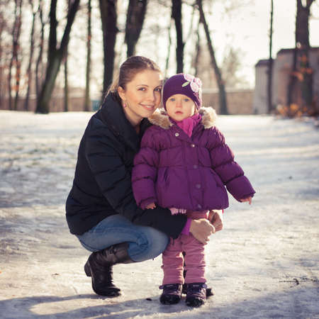 Young mother and her baby girl outdoors on a snowy winter day Stock Photo - 16987175