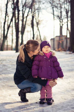 Young mother and her baby girl outdoors on a snowy winter day Stock Photo - 16987186