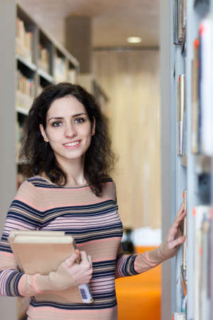 choose university: Pretty young woman in the library Stock Photo