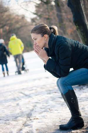 heartsick: Mujer deprimida joven sentado en un banco al aire libre en un d�a fr�o de invierno