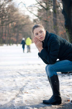 heartsick: Depressed young woman sitting on a bench outdoors on a cold winter day