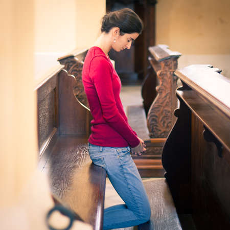 Young woman praying in a church Stock Photo - 17574162