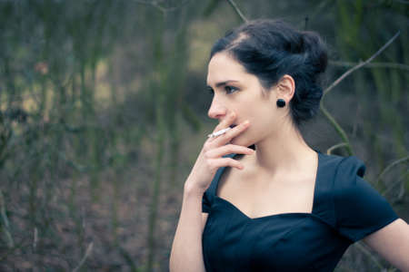 Portrait of a beautiful young woman smoking photo