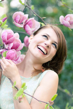 Spring portrait of a beautiful woman standing under a magnolia tree Stok Fotoğraf