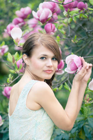 Spring portrait of a beautiful woman standing under a magnolia tree photo
