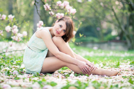 fresh start: Beautiful young woman sitting under a magnolia tree in bloom Stock Photo