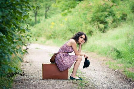 Het verlaten naar een onbekende bestemming: mooie jonge vrouw te wachten voor haar verbinding Stockfoto