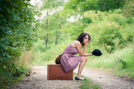 mujer con maleta: Dejando a un lugar desconocido: joven y bella mujer esperando su conexión Foto de archivo