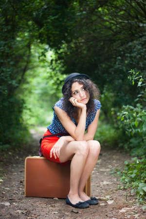 mujer con maleta: No para otra parte hermosa joven pensando en su próximo destino