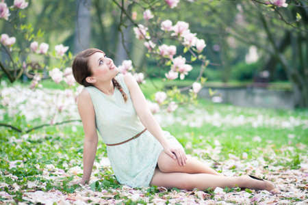 Beautiful young woman sitting under a magnolia tree in bloom photo
