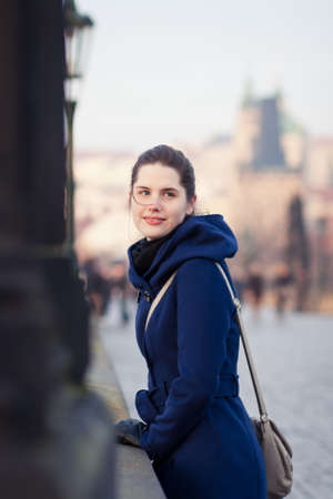 unesco in czech republic: Portrait of a young woman standing on the Charles Bridge with the panorama of Prague Castle in the background (Prague, Czech Republic)