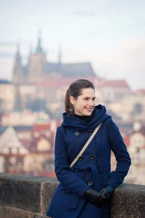 Portrait of a young woman standing on the Charles Bridge with the panorama of Prague Castle in the background (Prague, Czech Republic) photo
