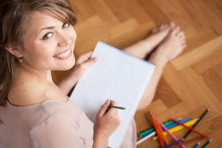 Pretty young woman  drawing for fun while sitting on the floor photo