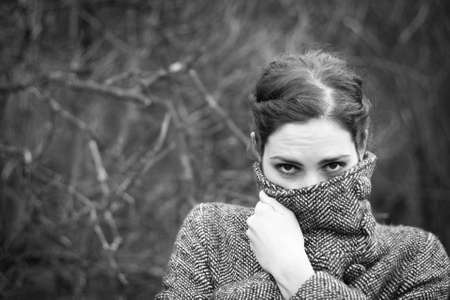 Cold weather: young woman wrapping up in her coat photo