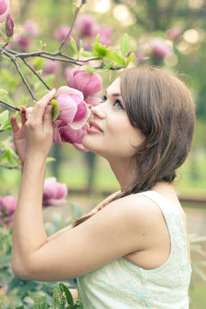 Beautiful young woman smelling freshly bloomed magnolias photo