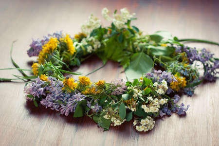 equinox: Closeup of a wreath of wild spring flowers on a wooden table Stock Photo