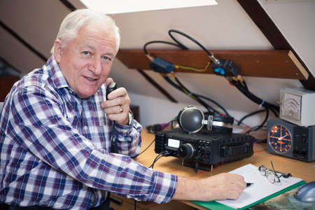 radio frequency: Enthusiastic middle-aged radio-amateur at his workplace Stock Photo