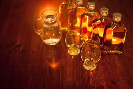 Whiskey tasting: sample bottles, glencairn glasses and a jug of water Stock Photo