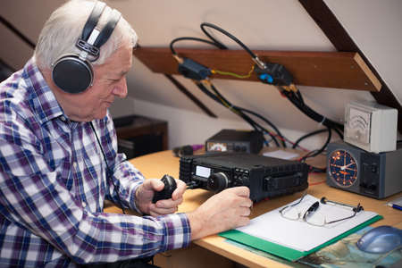 radio active: Enthusiastic middle-aged radio-amateur at his workplace Stock Photo