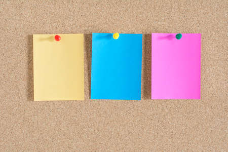 message board: Colorful notes paper on cork board background