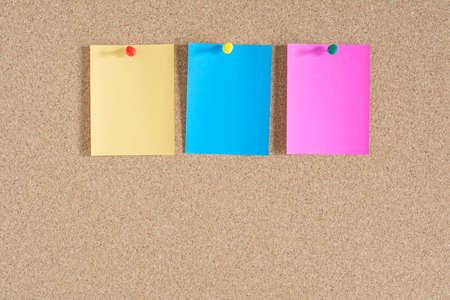 corcho: Notas papel colorido en el fondo tablero de corcho