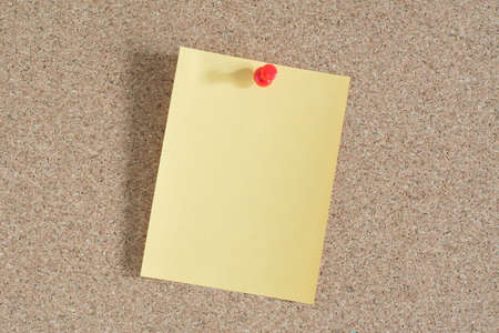 note paper: Yellow note paper on cork board background Stock Photo