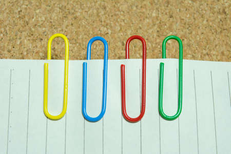 metal fastener: Paper clips of different colors used in the office. Stock Photo
