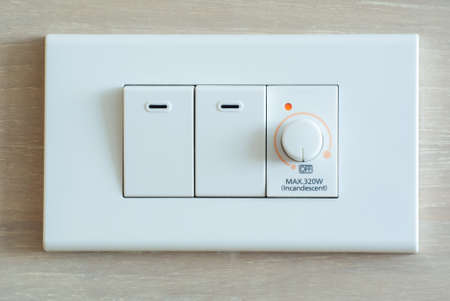 dimmer: Dimmer switch and light switch on switchboard Stock Photo
