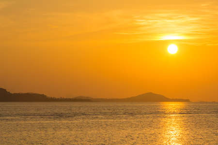 glows: beautiful sky and cloud with orange sunset and silhouette mountain reflecting glows in sea surface Stock Photo