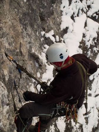 completely: Male climber ascending vertical cliff face. Winter