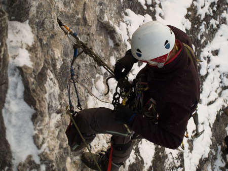 cliff face: Male climber ascending vertical cliff face. Winter