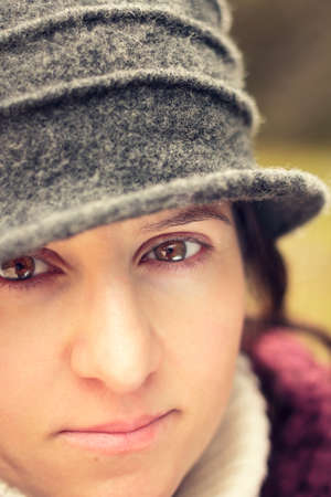 headshoot: young woman with hat looking at the camera