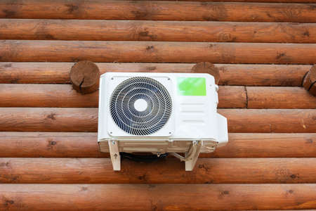 Outdoor air conditioning on the wooden wall of a log private house, climate, cools, heat, comfortable housing.